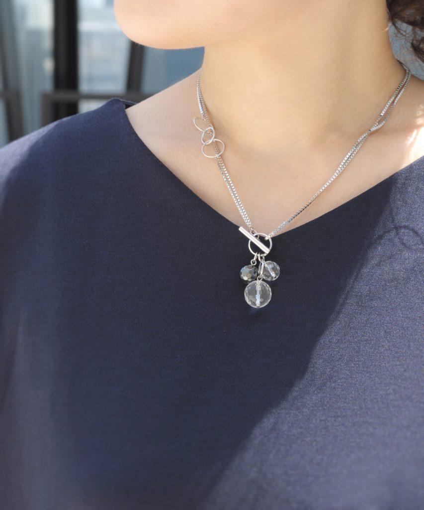 シルバーカラーのショートトップネックレスを着用した女性