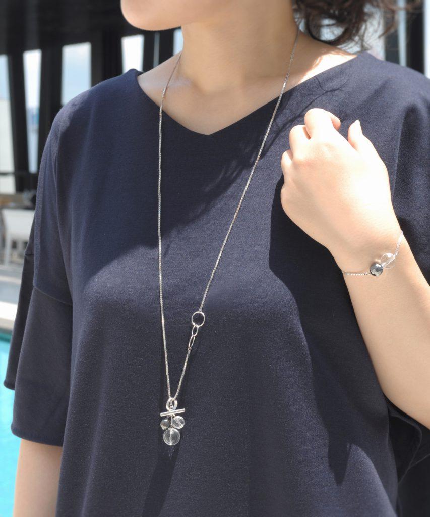 シルバーカラーのロングトップネックレスを着用した女性