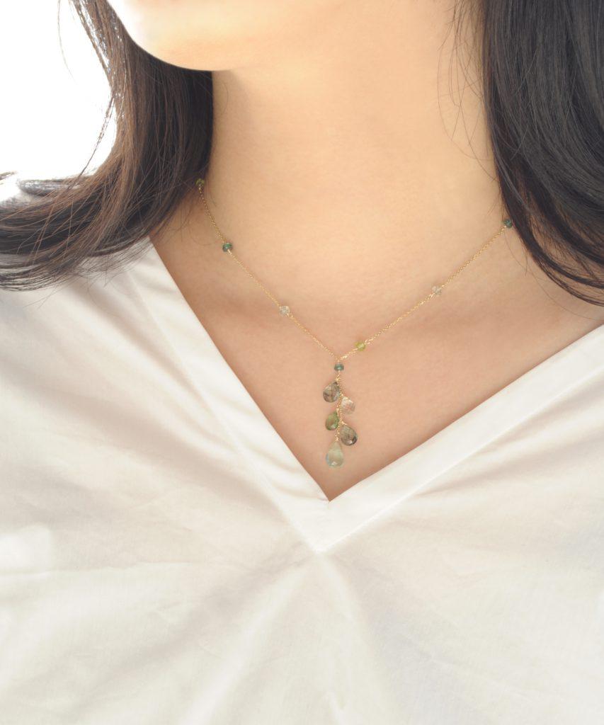 グリーングラデーションの天然石ネックレスを女性が着用
